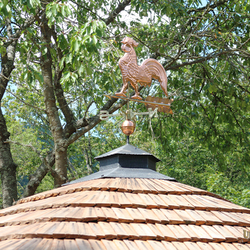 Copper rooster on a forged roof – summer gazebo near the family house