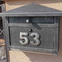 A wrought iron post box with a number sign